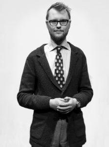 Svart-vit bild på man i glasögon, yllekofta och prickig slips står med händerna knutna framför vit bakgrund.