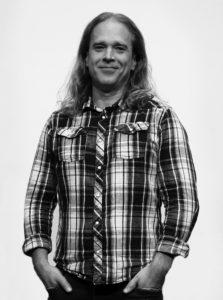svart vit bild på man med långt hår som står med händerna i fickorna. Rutig skjorta.