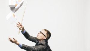 Hans Rosling fångar vita lådor med orange gubbar på som faller uppifrån