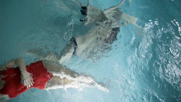 Två människor i en simbassäng, ena har röd simdräkt, ansikten otydliga